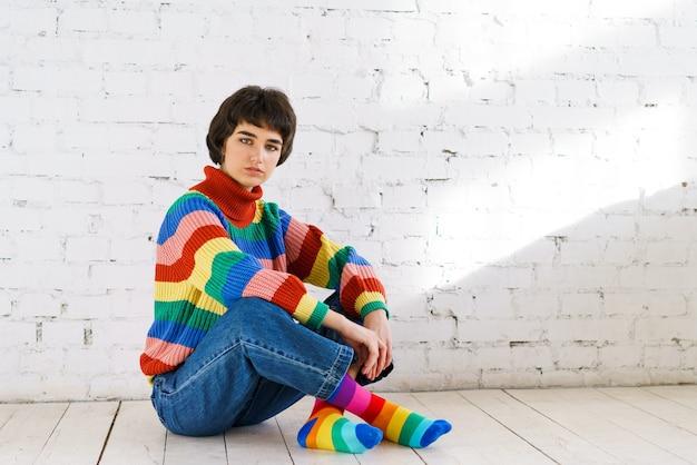虹色のlgbtセーターを着た若いレズビアンの女性が明るい部屋のソファに座って性的権利...