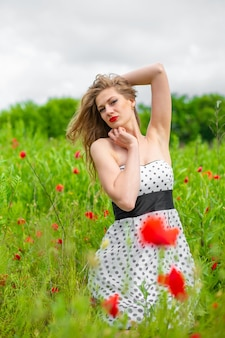 Молодая длинноволосая девушка наслаждается красками природы на цветущем маковом поле в жаркий летний день.