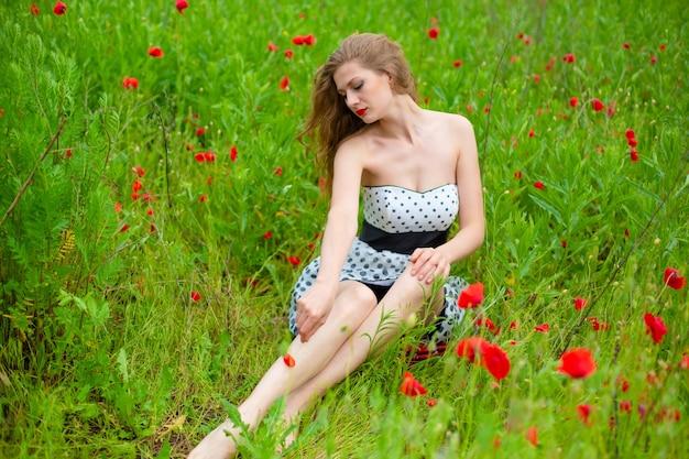 長い髪の少女は、暑い夏の日に咲くケシ畑で自然の色を楽しんでいます。