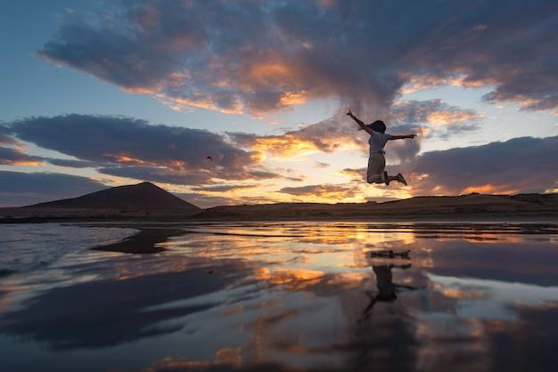 若い長髪の女性が日没時に楽しくジャンプします