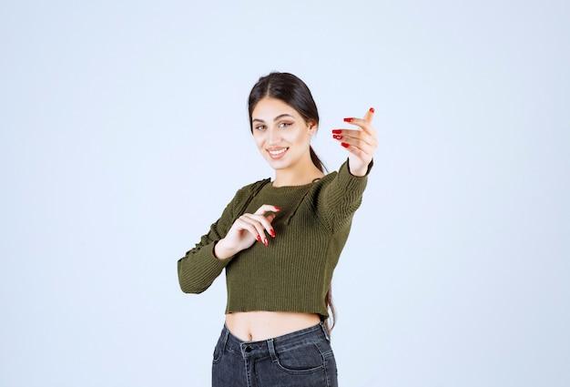 緑の若い素敵な女性モデルが誰かに来るように呼びかけます