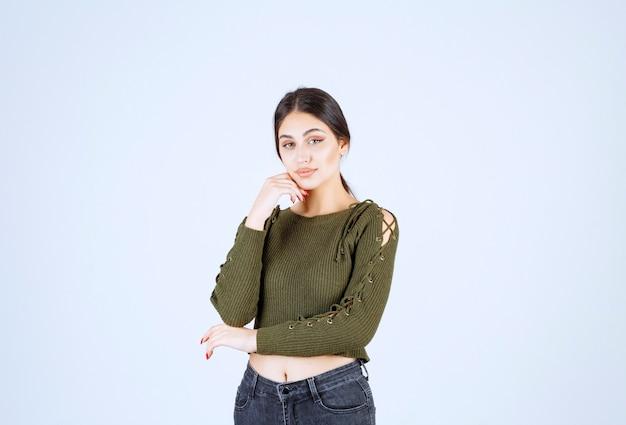 Модель молодой прекрасной женщины в зеленом, смотрящей в камеру