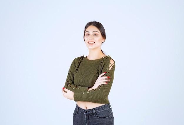 緑の立っている腕の若い素敵な女性モデルが交差しました