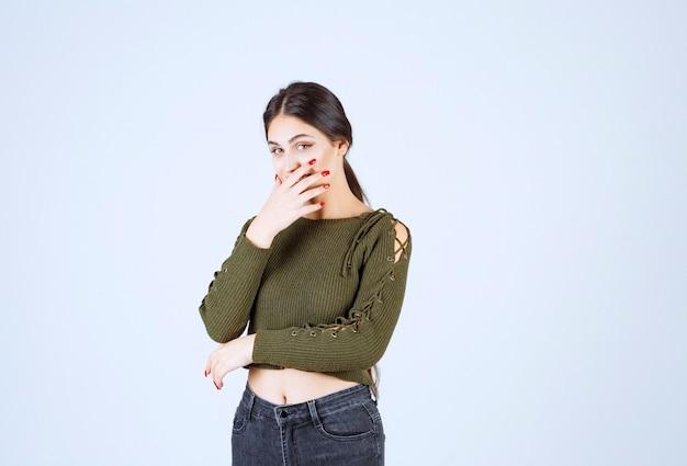 彼女の笑いを保持しようとしている緑の若い素敵な女性モデル