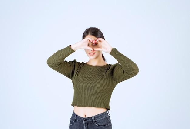 흰색 배경에 심장 기호를 만드는 젊은 사랑스러운 여자 모델