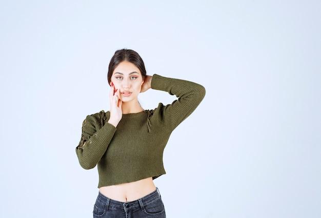 Молодая милая женщина модель позирует перед камерой на белом фоне