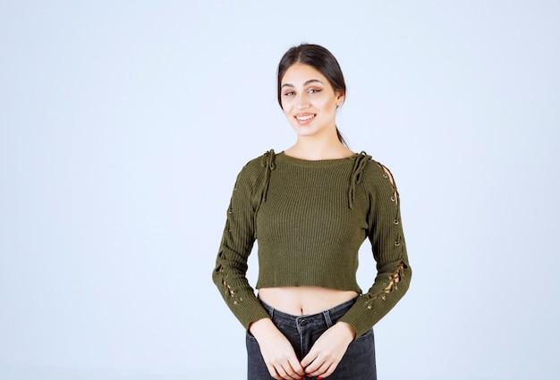 Молодая милая женщина модель счастливо улыбается на белом фоне