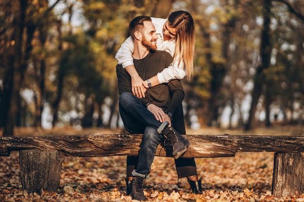 Молодая влюбленная пара, сидя на деревянной скамейке в лесу. мужчина и женщина обнимаются и улыбаются в осеннем парке