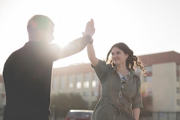 젊은 남성과 여성 커플은 야외에서 하이파이브를 하고, 성공적인 행복한 관계 개념을 제공합니다.