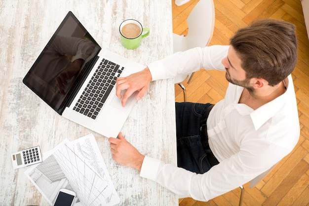 Молодой архитектор мужского пола, работающий дома с портативным компьютером.