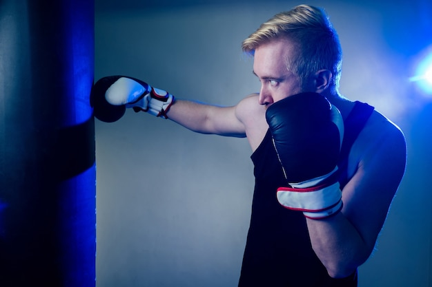 若い男性ボクサーがジムでスポーツをしています。ボクサー、暗い背景のボクシンググローブ。男がストライキ