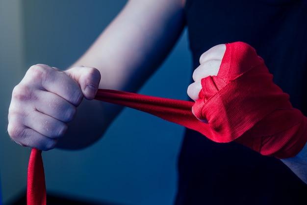 若い男性ボクサーがジムでスポーツをしています。ボクサー、暗い背景にボクシンググローブを着用します。男がストライキ。手に赤い包帯