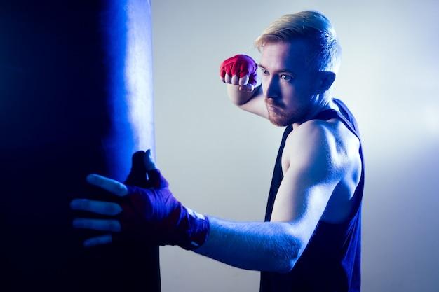 젊은 남성 권투 선수가 체육관에서 운동을 하고 있습니다. 권투 선수는 어두운 배경에 권투 장갑을 끼고 있습니다. 남자가 친다. 손에 빨간 붕대