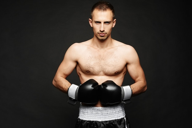 Молодой боксер мужского пола со спортивным прекрасным телом в боксерских перчатках, изолированных на темной стене