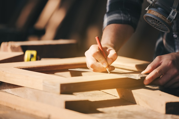 全体的に働いている若い男性の大工ビルダーは、ワークショップでフライス盤を備えた木製のバーに匹敵します、