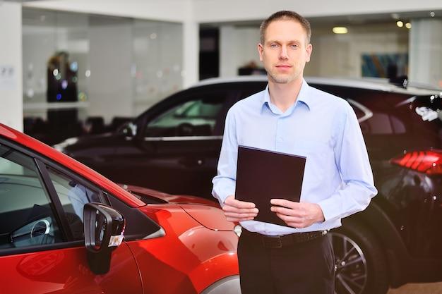 자동차 대리점 또는 자동차 상점의 젊은 남성 컨설턴트 관리자가 손에 태블릿을 들고 자동차 표면에 서 있습니다.