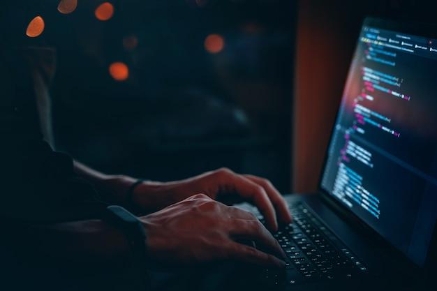 Молодой разработчик программирует кодовый скрипт поздно ночью с красивыми городскими огнями.