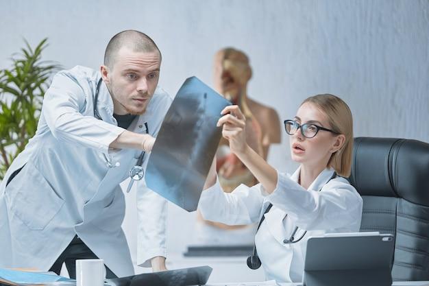 Молодой врач-мужчина консультируется с коллегой по поводу результатов рентгеновского обследования.