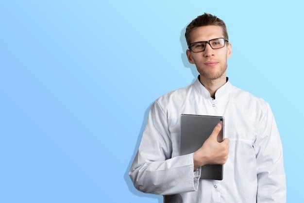 色の壁の近くに立って孤立したデジタルタブレットを保持している若い男性医師