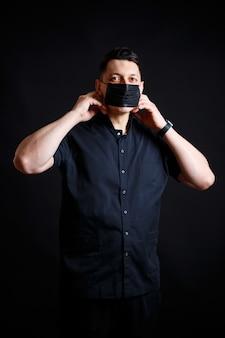 黒い手術着を着た若い男性医師は、ウイルスから身を守るために黒いマスクを着用します。黒の背景に分離