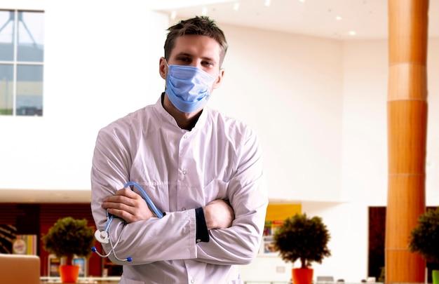 病院、診療所で保護マスクを身に着けている制服を着た若い男性医師