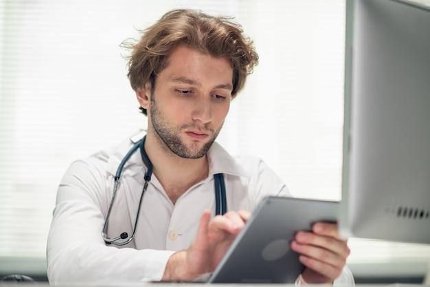 Молодой врач-мужчина сидит за своим столом в офисе и проверяет расписание на своей вкладке.