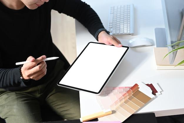 젊은 남성 그래픽 디자이너가 워크 스테이션에서 디지털 태블릿을 사용하고 있습니다.