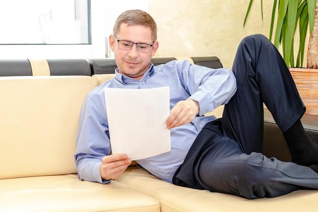青いシャツを着た眼鏡をかけた若い男性マネージャーが、彼のモダンなオフィスのソファに横たわっています。ソファでくつろぎながらドキュメントを読みます。