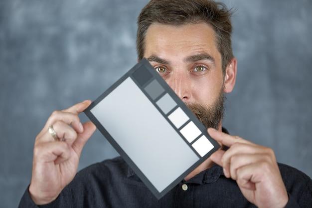 젊은 남성 모델이 얼굴 근처에 중간 회색 음영이 있는 컬러 체커를 들고 있습니다.