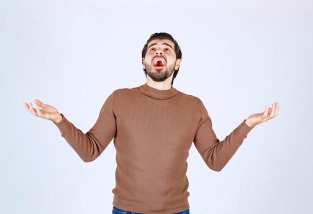Молодая мужская модель в коричневом свитере, стоящая над белой стеной.