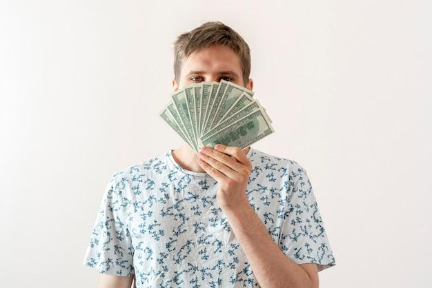 ドルの現金通貨のパックを保持し、顔をカバーする若い男性の人、成功の概念