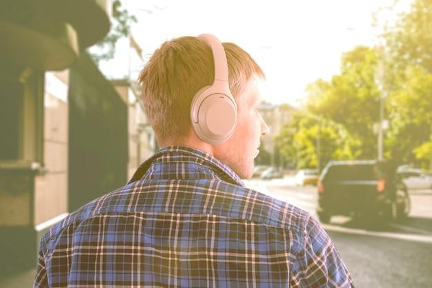 Молодой человек мужского пола слушает наушники, наслаждается звуком, расслабляется и расслабляется