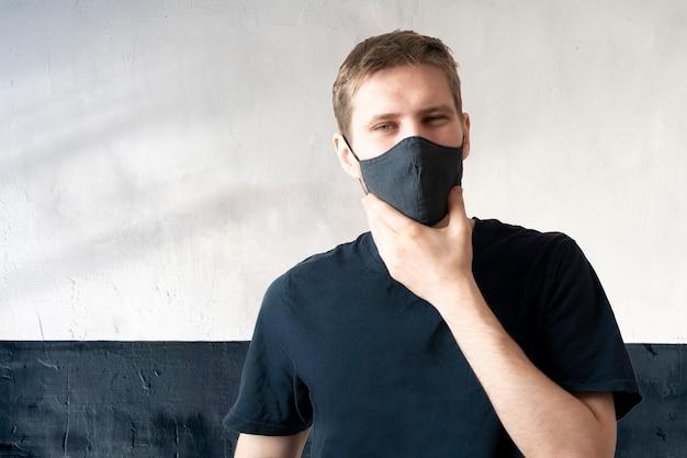 若い男性は、covid-19ウイルス、カジュアルなライフスタイルの服から保護するために黒いテキスタイルマスクを着用します