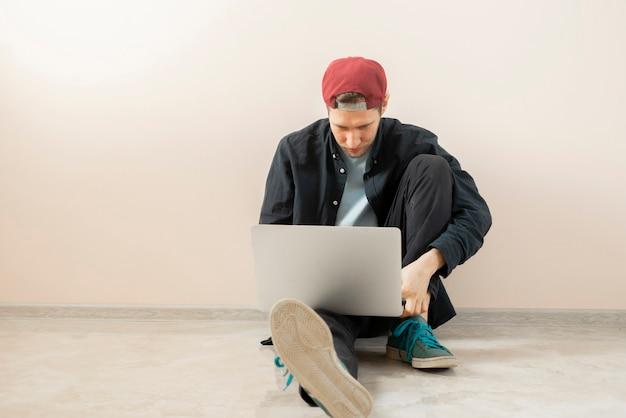 ラップトップ、隔離された壁の近くに座っているオンラインフリーランサーのライフスタイルで自宅で働く若い男性