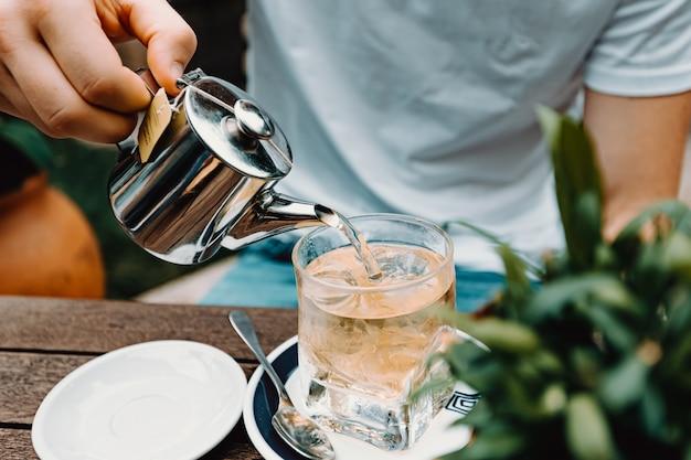 Молодой мужчина готовит чай в современном баре