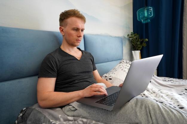Молодой программист работает с ноутбуком дома на кровати