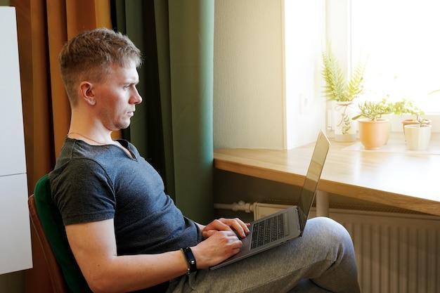 Молодой программист работает с ноутбуком дома
