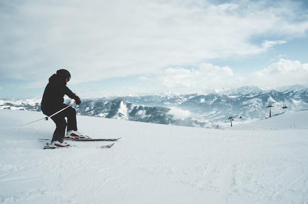 Молодой мужчина катается на лыжах в горах, покрытых снегом