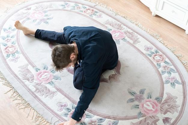 Молодой мужчина растягивается дома, делая некоторые фитнес-упражнения
