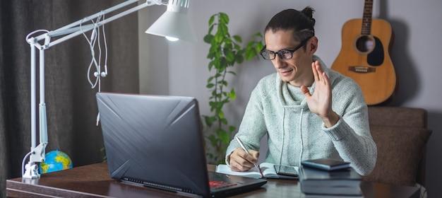 Молодой студент-мужчина учится на онлайн-уроке, используя ноутбук ночью при свете лампы в комнате