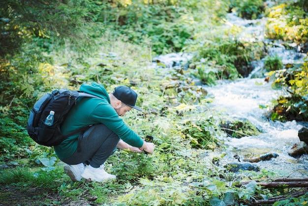 젊은 남성 관광객이 숲에서 스마트폰 카메라로 사진을 찍습니다. 관광, 활동적인 라이프 스타일