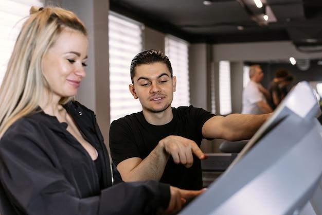 젊은 남성 트레이너가 체육관에서 러닝 머신을 올바르게 사용하는 방법을 보여줍니다.