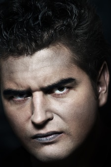 暗い背景の上の若い男性の吸血鬼