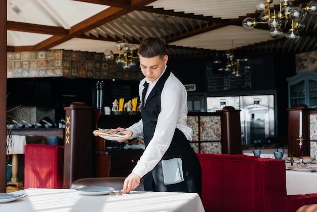 세련된 제복을 입은 젊은 남성 웨이터가 아름다운 미식 레스토랑에서 테이블을 서빙하고 있습니다. 최고 수준의 레스토랑 활동.