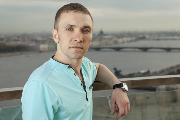 Молодой человек 27 лет, европеец, славянин, русский, одет в бирюзовую рубашку с короткими рукавами.