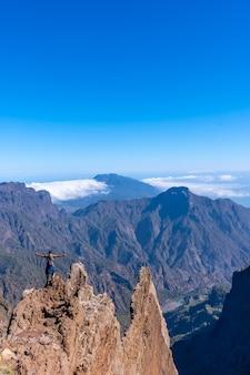 Молодой человек после завершения похода на вершину вулкана кальдера-де-табуриенте возле роке-де-лос-мучачос смотрит на невероятный пейзаж ла-пальма, канарские острова. испания