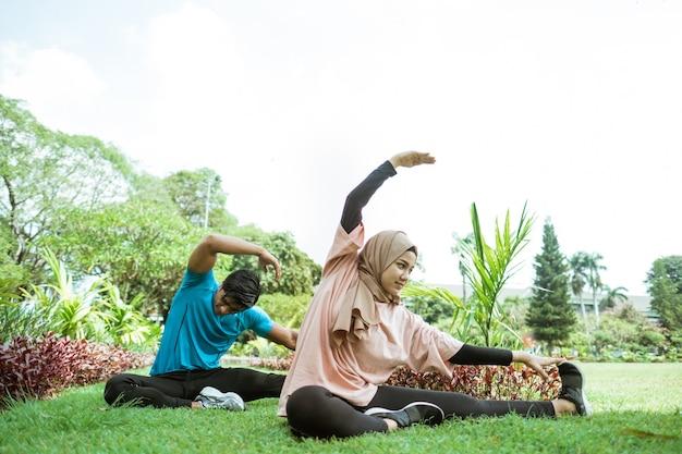 公園での屋外運動時に脚の筋肉を一緒に訓練する動きをしているスカーフの若い男と少女