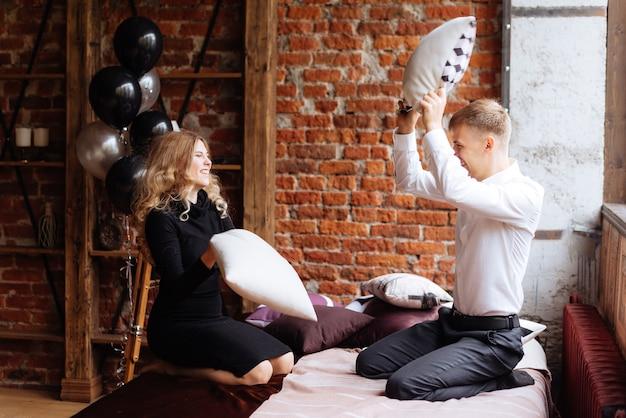 若い男と女がロフトスタイルの部屋のベッドで枕と戦う