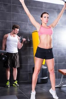 ジムで運動している若い男性と若い女性。