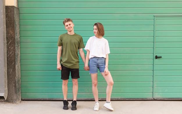 Молодой человек и привлекательная девушка держатся за руки на бирюзе